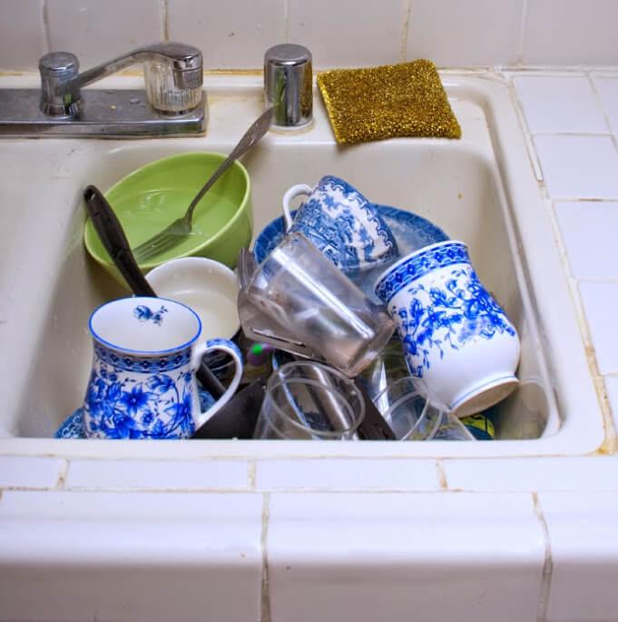 platos, tazas, cuencos y cubiertos limpios, pero apilados en un fregadero